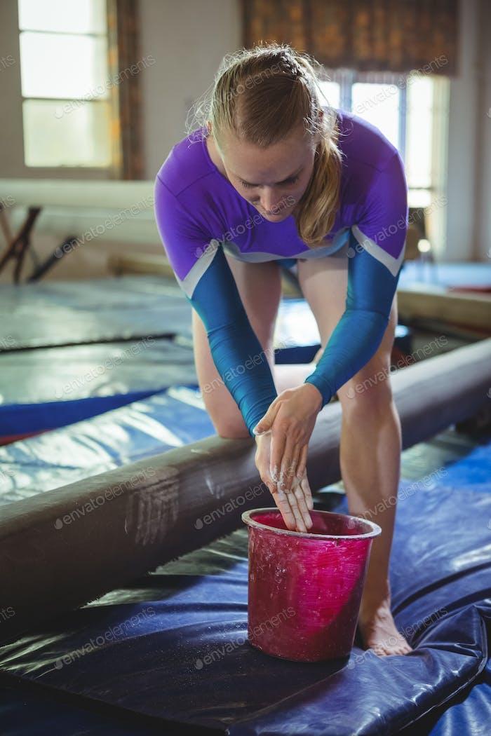 Female gymnast applying chalk powder on her hands before practicing