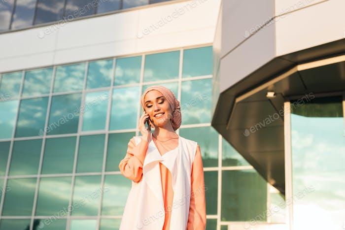 schöne junge arabische Frau im Gespräch auf Handy