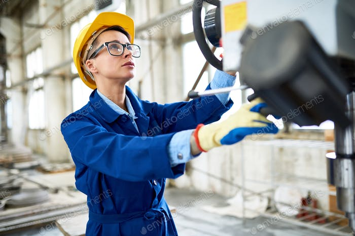Modern Woman Setting Machines at Factory
