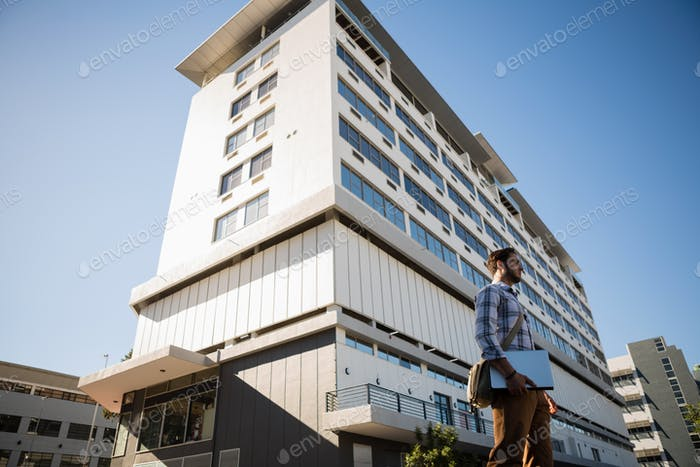 Man holding laptop while standing by building in city