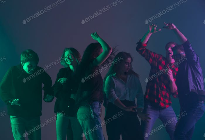 Cheering dance party, performance concept. Crowd shadow of people dancing with neon lights raised