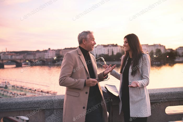 Man and woman business partners standing by a river in city of Prague at dusk, talking.