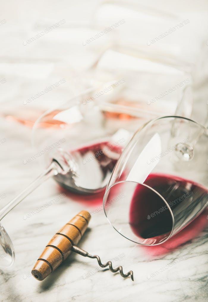 Roter und Rosenwein in Gläsern über grauem Marmorhintergrund