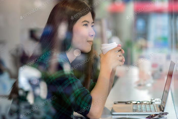 Portrait of asian businesswoman in casual suit drinking and working
