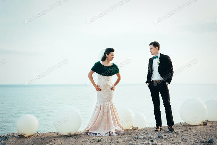 the groom in a brown suit and the bride in an ivory dress