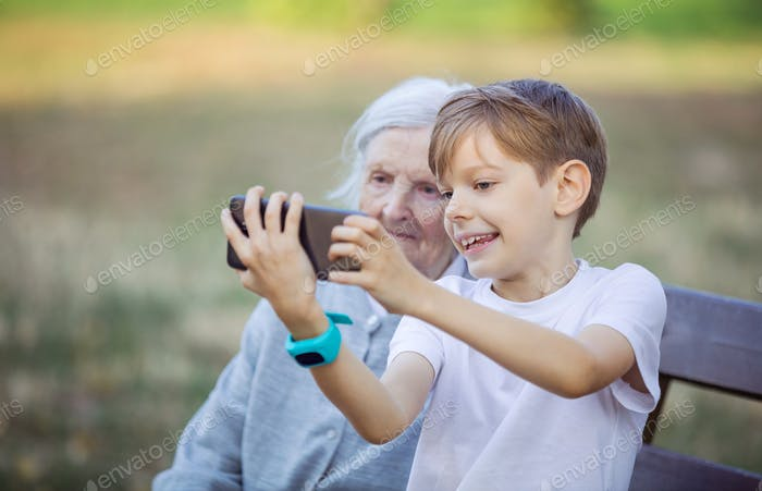 Young boy and his great grandmother using smartphone to take selfie.
