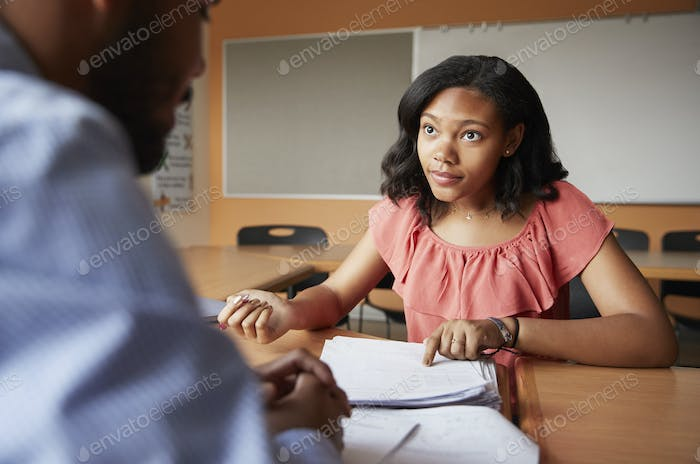 High School Tutor Giving Female Student One To One Tuition At Desk