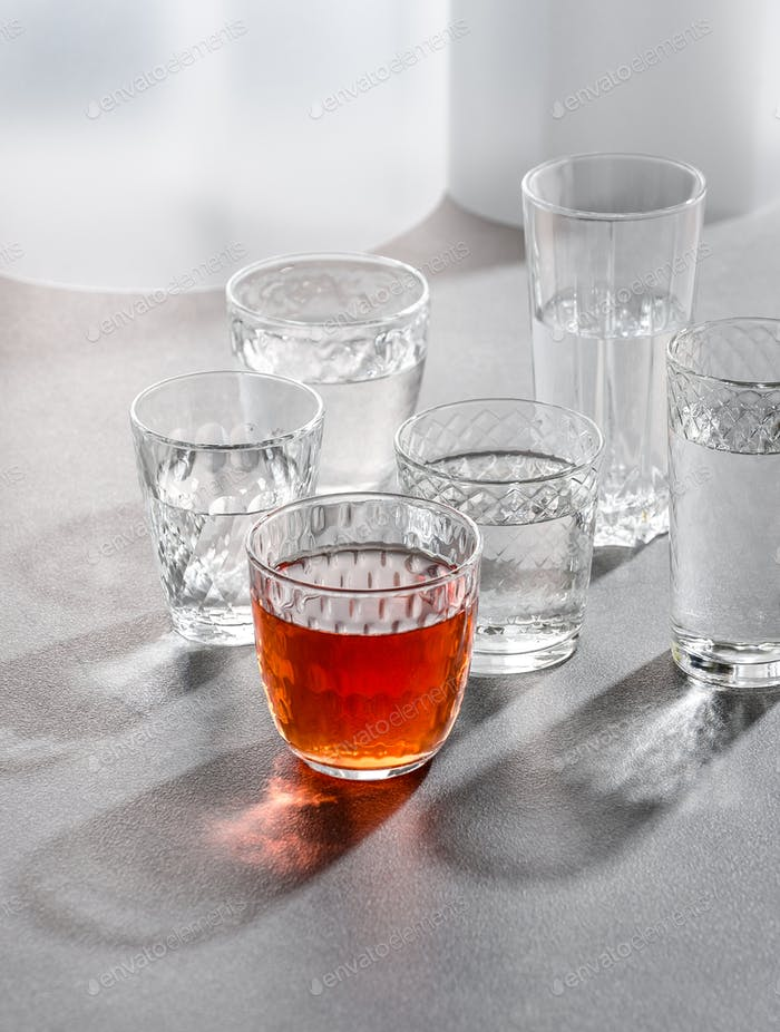 Glasses with water and a drink on a gray stone table. Shooting w