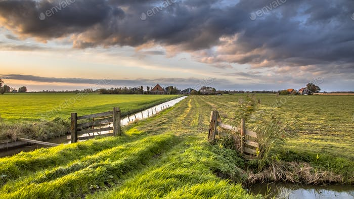 Cloudscape over gate in lowland meadow