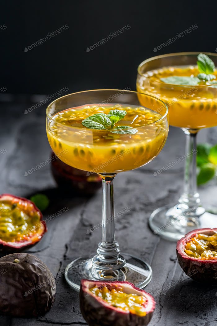 Alcoholic cocktail with fresh passion fruit and mint on black background.