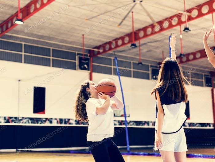 Teenager-Mädchen spielen ein Basketball machen einen Pass