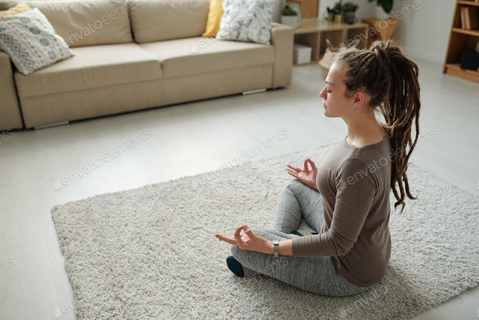 Girl in activewear listening sitting in pose of lotus on carpet while meditating