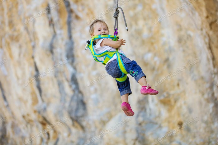 Little girl in climbing gear hanging on rope