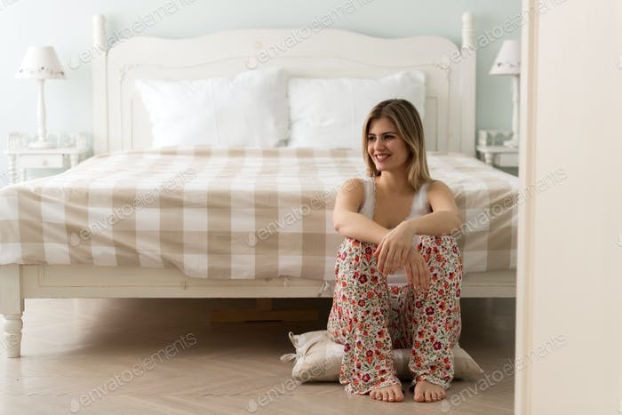 Young happy beautiful woman sitting in bedroom