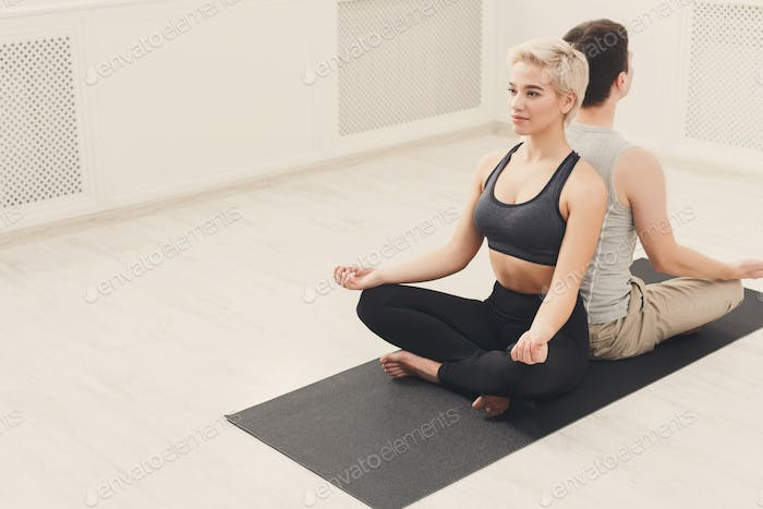 Young couple meditating together, back to back