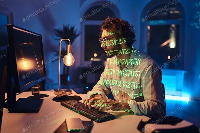 Freelancer caucásico con gafas y computadora trabaja en la oficina oscura