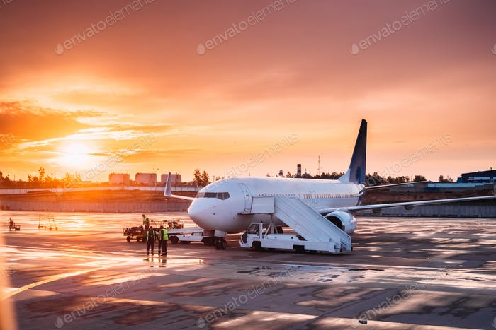 Aircraft Plane Boarding Passengers In Airport In Sunny Sunset Su