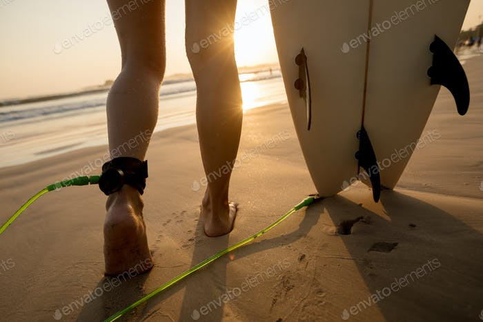 Surfer legs with surfboard on beach