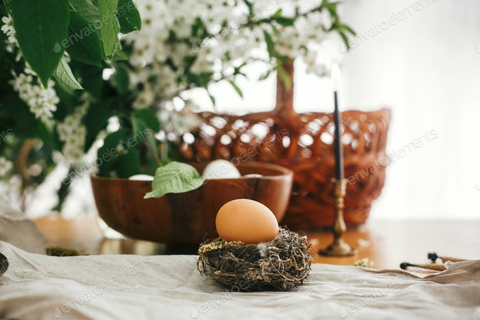 Natural Easter eggs, vintage candle and wicker basket on rustic table with cherry flowers