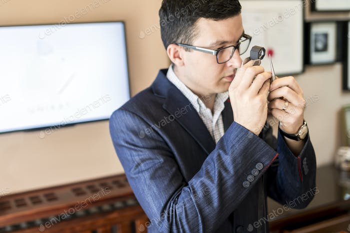 Jeweler looking at diamond through loupe