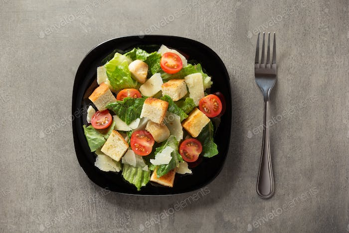 caesar salad in plate at table