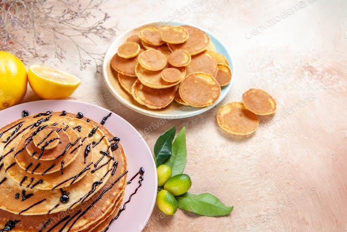 Vorderansicht von einfachen und dekorierten klassischen Pfannkuchen, die mit Früchten auf buntem Hintergrund verziert sind