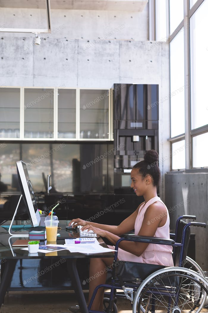 Young disabled businesswoman working on computer at desk in the mordern office