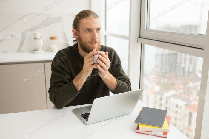 Young man sitting at the table with cup in hand and laptop dreamily looking at window