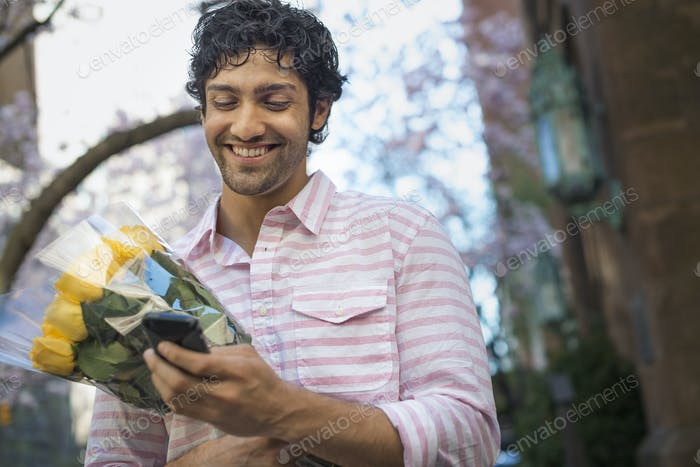 City in spring, A young man in a park using a mobile phone with a bunch of yellow roses,