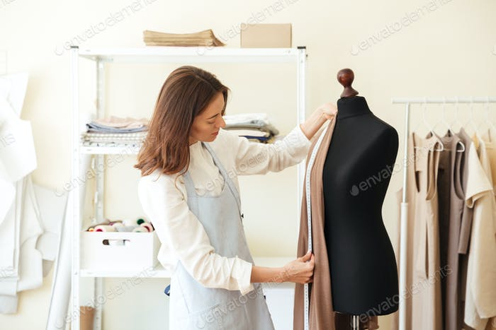 Seamstress measuring fabric on black dummy