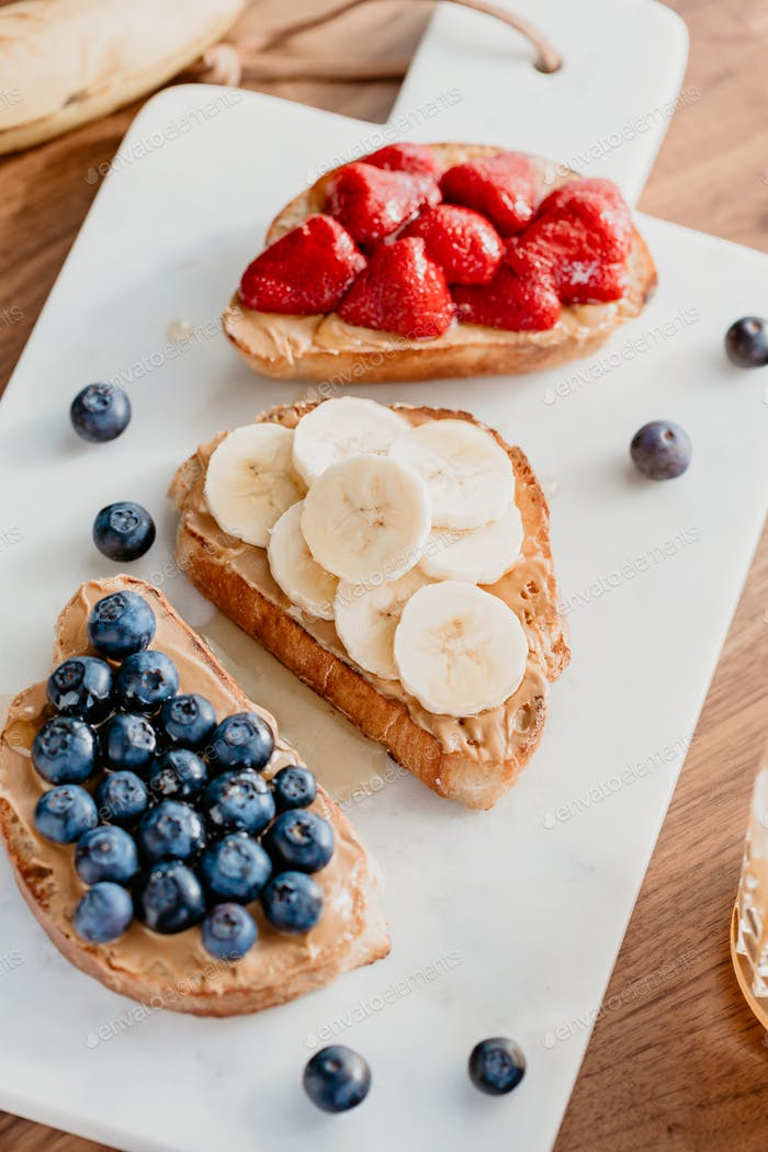 Toasts with peanut butter, blueberry, strawberry and banana.