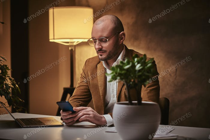 Bald confident and smiling european handsome businessman sitting in the office
