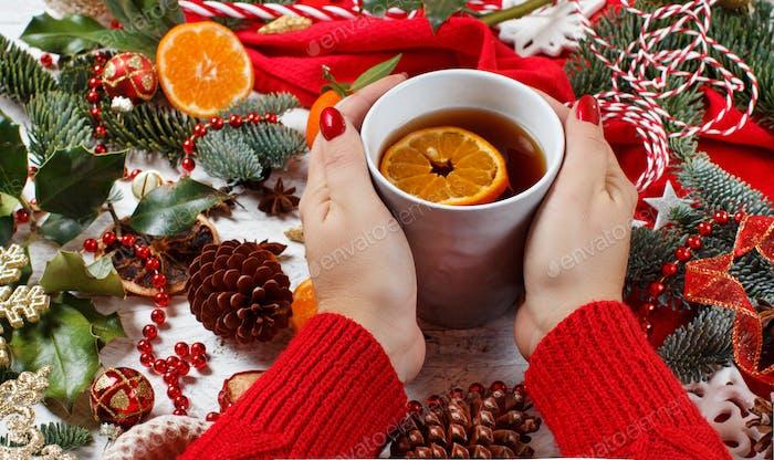 Girl keeping tea mug with Christmas with decorations around