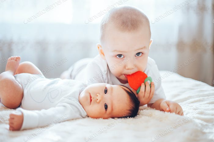 baby child lying on belly weared diaper with teether