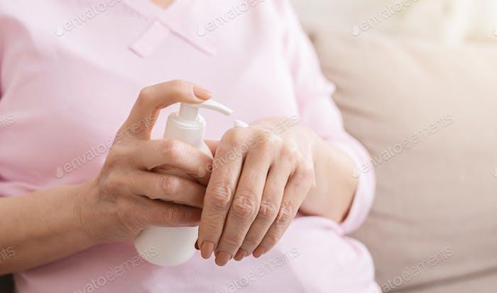 Hände Senior Frau mit Feuchtigkeitscreme Nahaufnahme