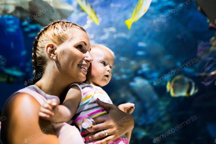 Mother and her child watching sea life in oceanarium