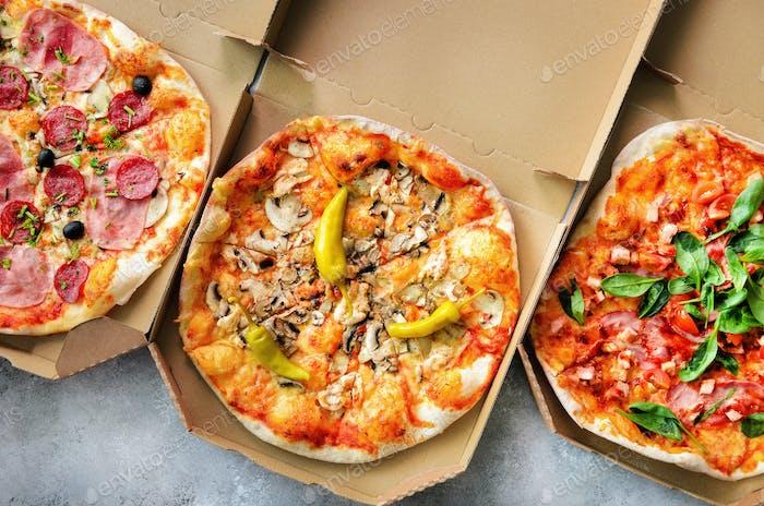 Frische Pizza im Lieferkarton auf grauem Betonuntergrund. Draufsicht, Kopierbereich