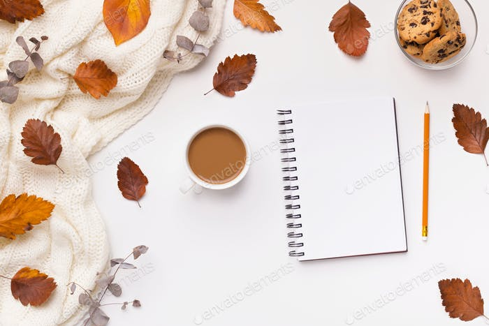 Notebook with copy space, coffee and fallen leaves on white