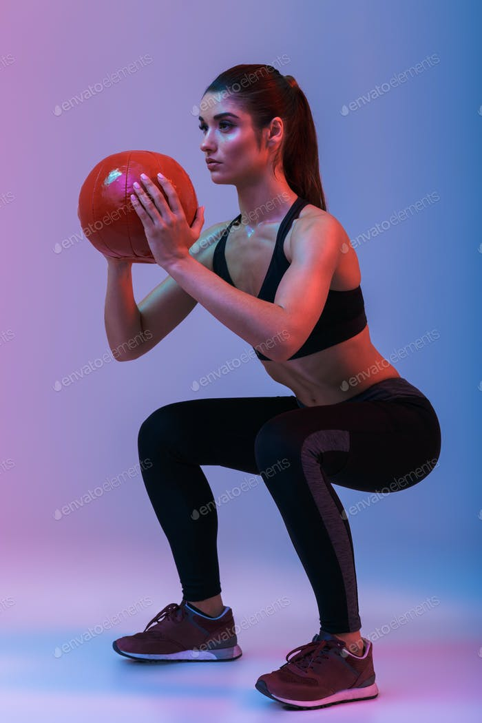 Concentrated young sports woman make exercises with ball.
