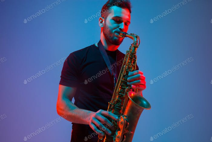 Young caucasian jazz musician playing the saxophone in neon light