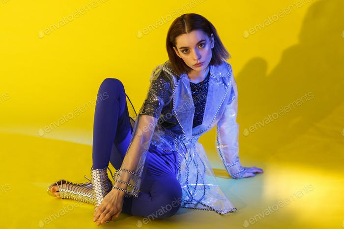 young fashionable female model in trech isolated on yellow background