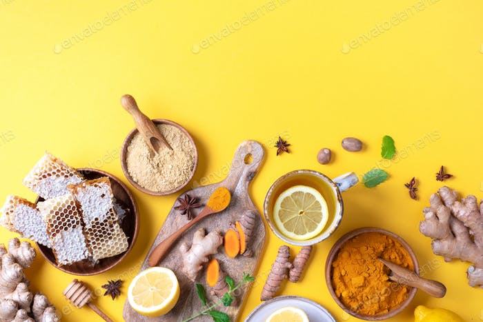 Organic ingredients for turmeric hot tea on yellow background. Antiviral beverage. Healthy ayurvedic
