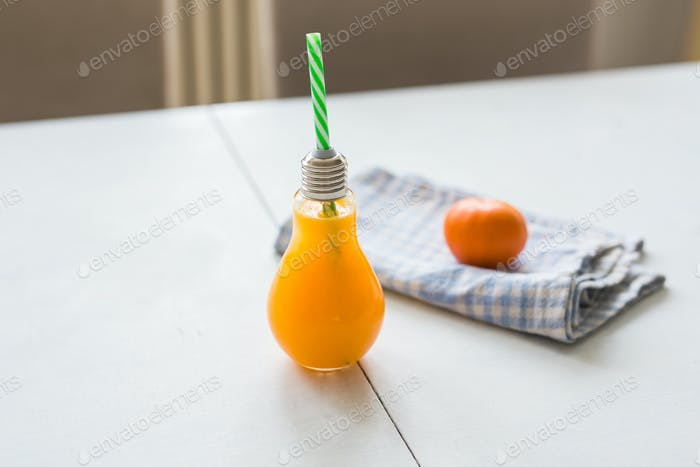 Orange juice in a glass in the form of a light bulb