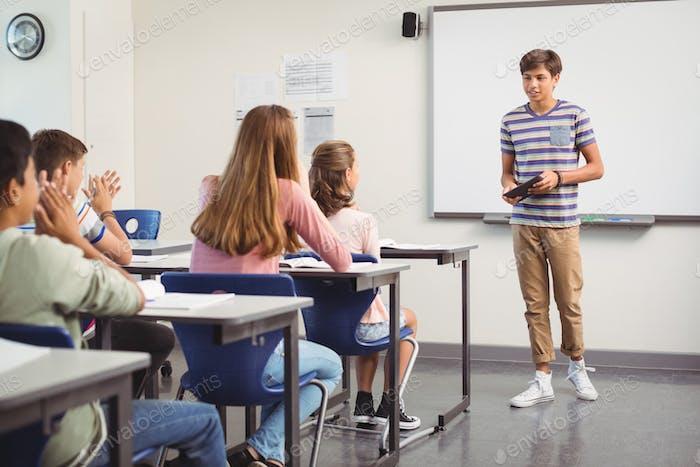 Schoolboy giving presentation in classroom