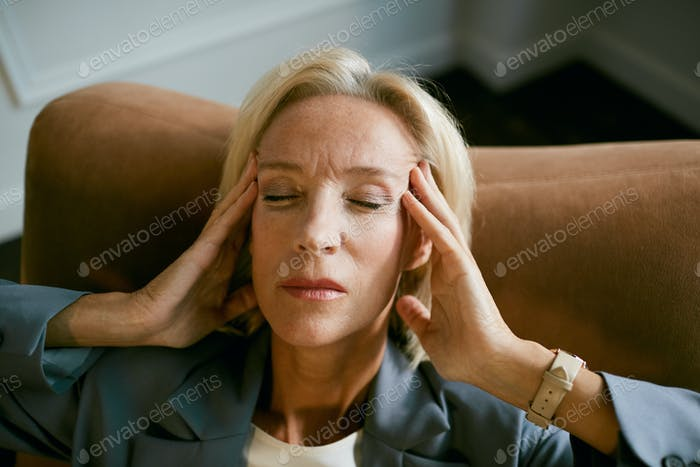 Mature Businesswoman Suffering from Headache