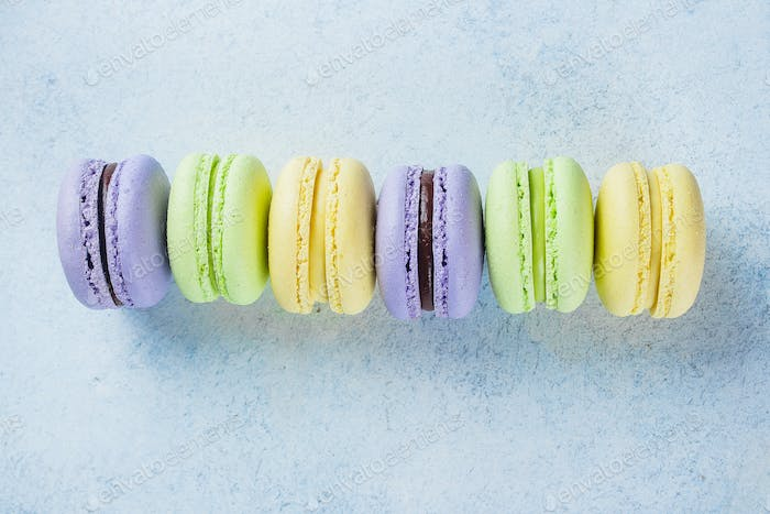 Cake macaron or macaroon on light blue background from above. Pastel colors, almond cookies
