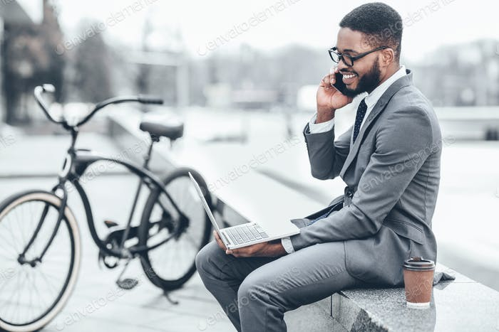 Businessman with bicycle nearby having business talk on phone