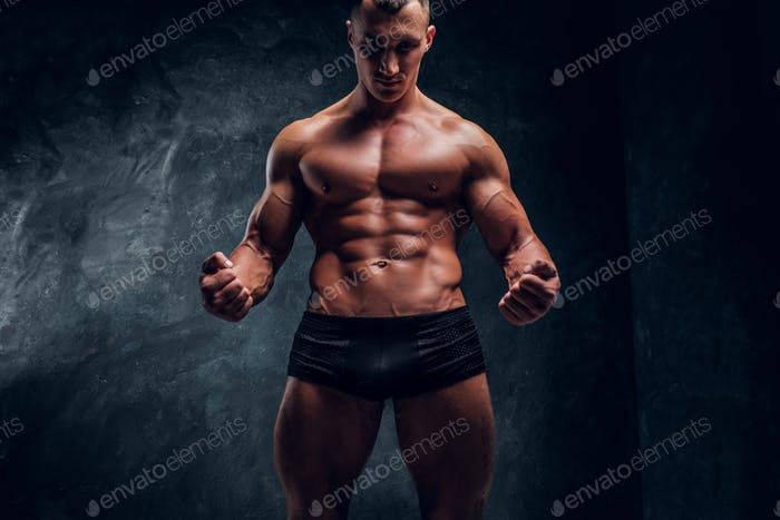 Athletic man in underwear showing his perfect pumped body. Studio photo with dark wall background