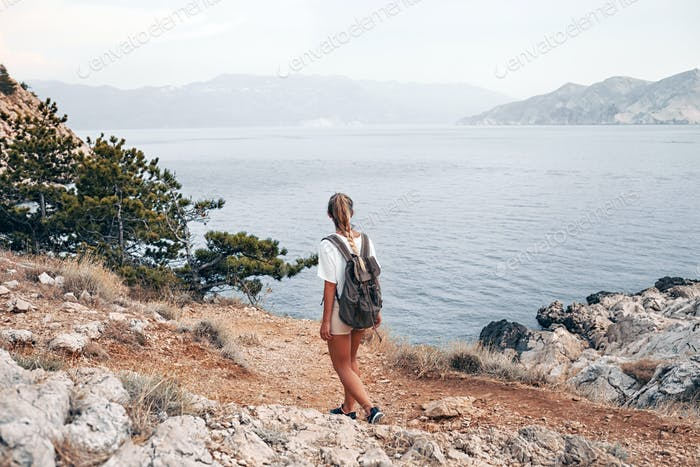 Hiker girl with backpack hiking on trail along sea bay