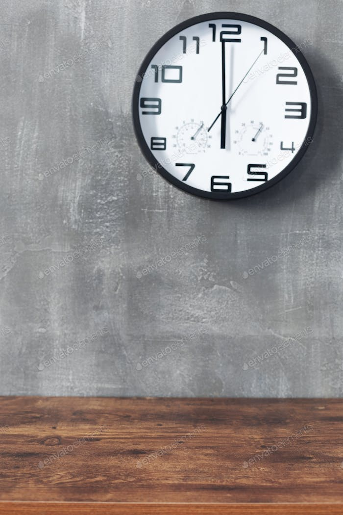 wall clock and table near concrete background